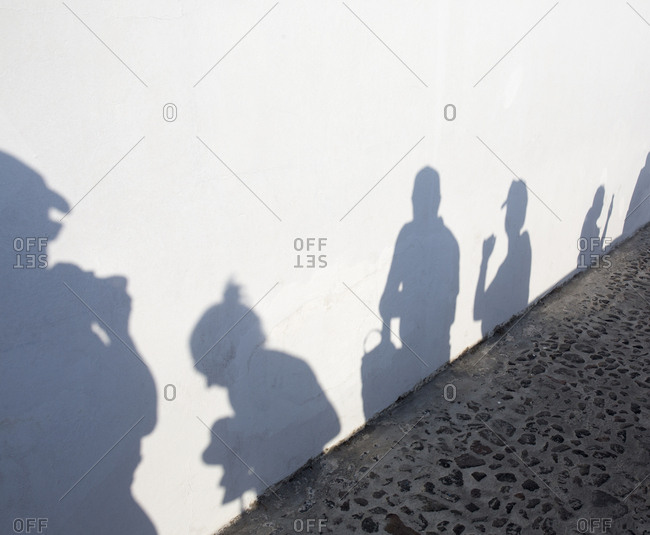 Tourist's shadow on white wall as they prepare to take photographs of sunset in Fira village, Santorini, Greece