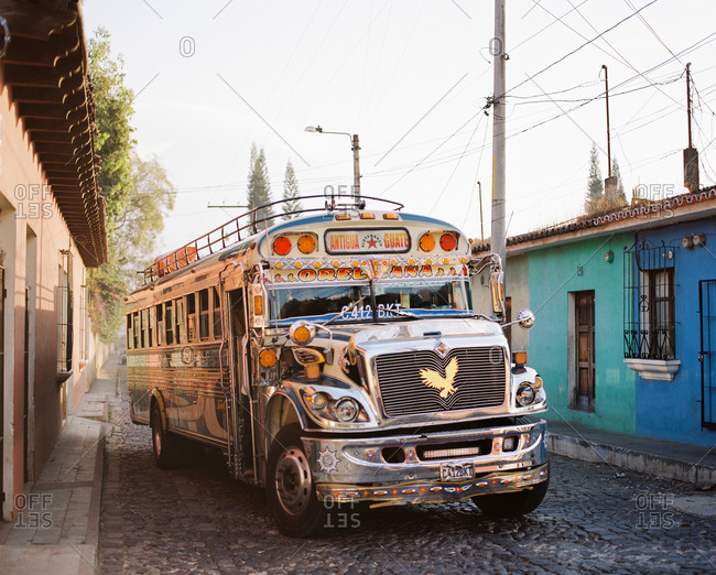 Antigua, Guatemala - January 16, 2019: A colorful chicken bus parked on old cobblestone street