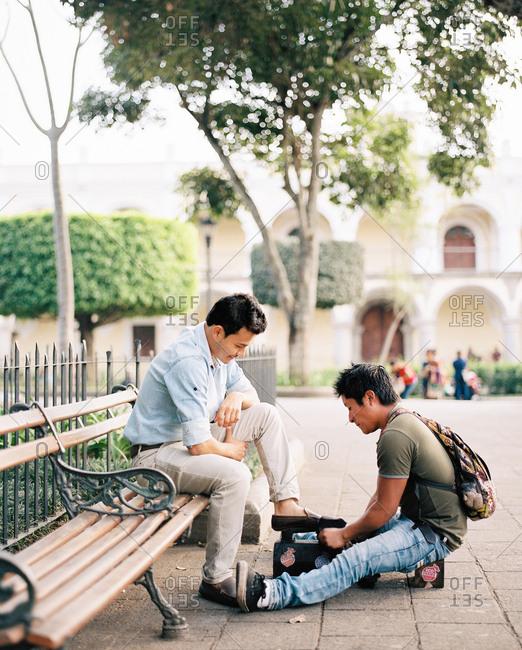 Antigua, Guatemala - January 17, 2019: Man having his shoes shined on a park bench