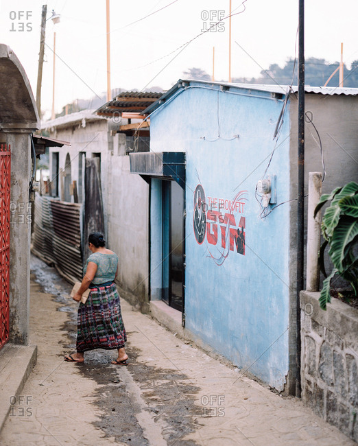 Guatemala - January 17, 2019: Woman walking by gym on small street in a Guatemalan town