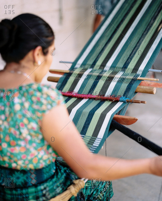 Woman weaving on a loom in San Juan La Laguna, Guatemala