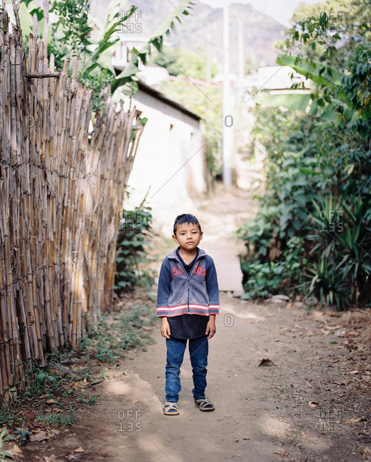 Guatemala - January 17, 2019: Portrait of a young Guatemalan boy standing on dirt path