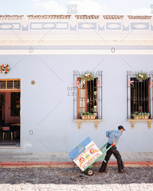Antigua, Guatemala - January 17, 2019: Man walking with ice cream cart on cobblestone street
