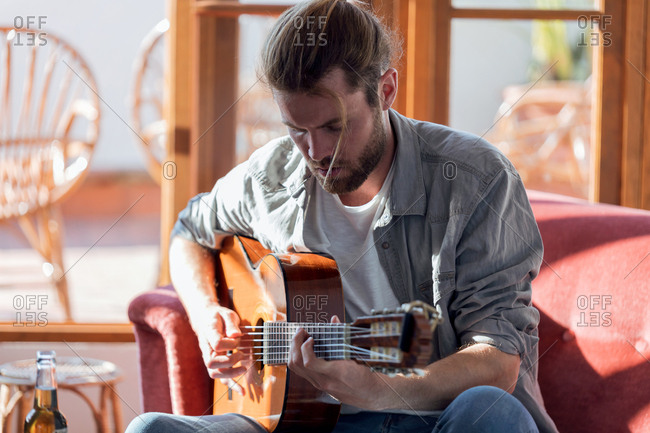 Shot of hipster young man playing the acoustic guitar while sitting on the couch in the living room at home.
