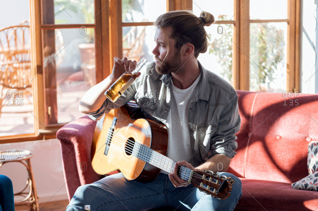 Shot of hipster young man drinking beer while playing the acoustic guitar and sitting on the couch in the living room at home.