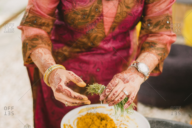 Woman preparing turmeric for Haldi ceremony in a Hindu wedding