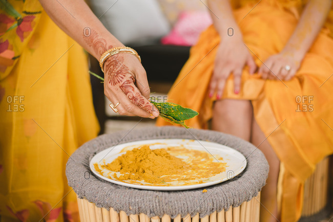 Woman putting turmeric on leaves for Haldi ceremony in a Hindu wedding