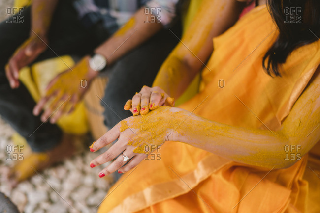 Bride rubbing turmeric on her hands and arms as part of a Haldi ceremony