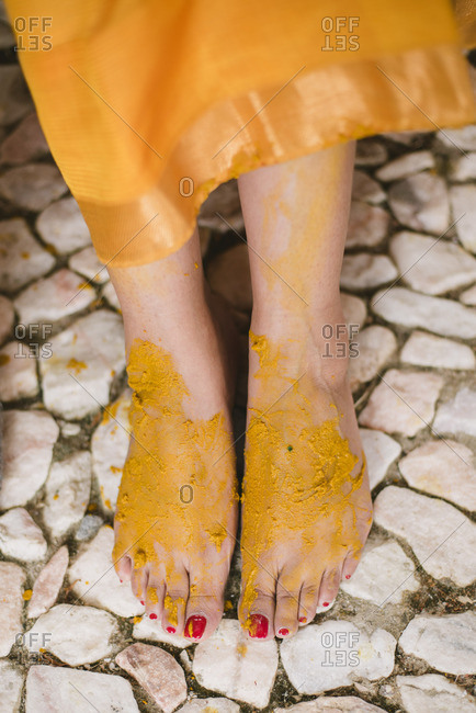 Bride's feet covered in turmeric on her hands and arms as part of a Haldi ceremony