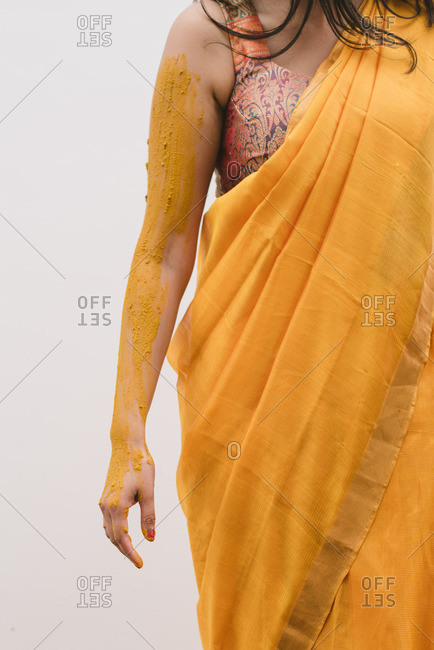 Bride's arm covered in turmeric on her hands and arms as part of a Haldi ceremony