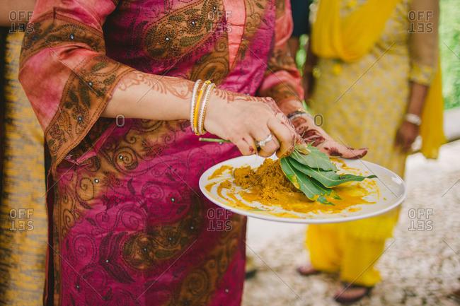 Woman with henna tattoos preparing turmeric for Haldi ceremony in a Hindu wedding