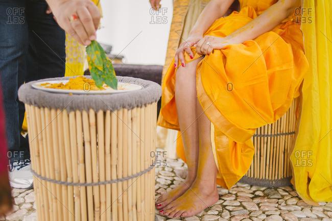 Bride wearing yellow sari during a Haldi ceremony