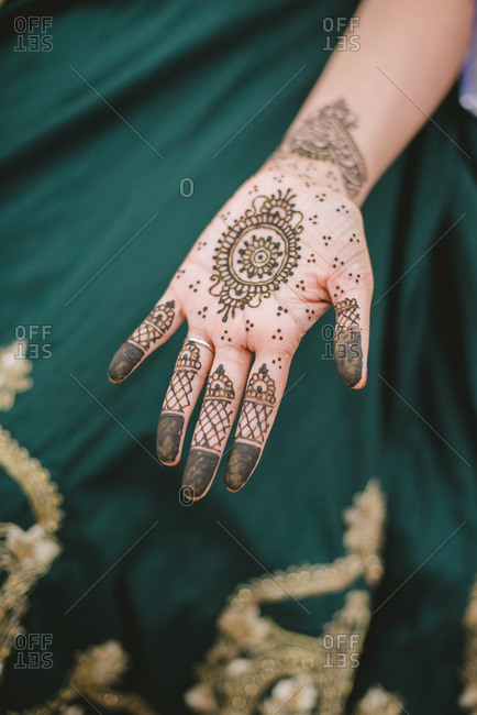 Bride showing her hand covered in henna before wedding