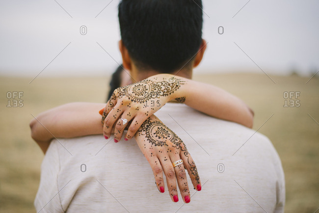 Bride wrapping her henna covered hands around her husband