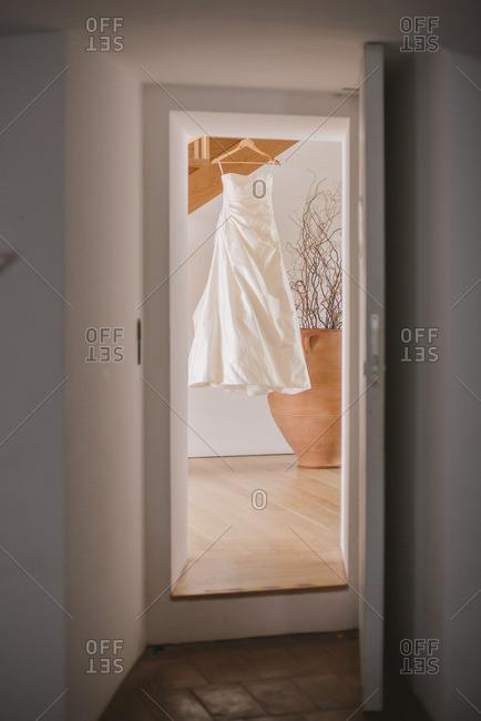White wedding gown seen hanging on hanger through open doorway
