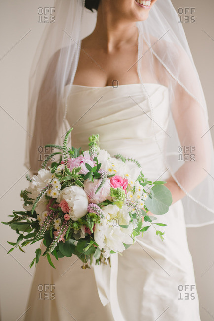 Bride wearing a traditional gown and veil and holding a beautiful bouquet of flowers