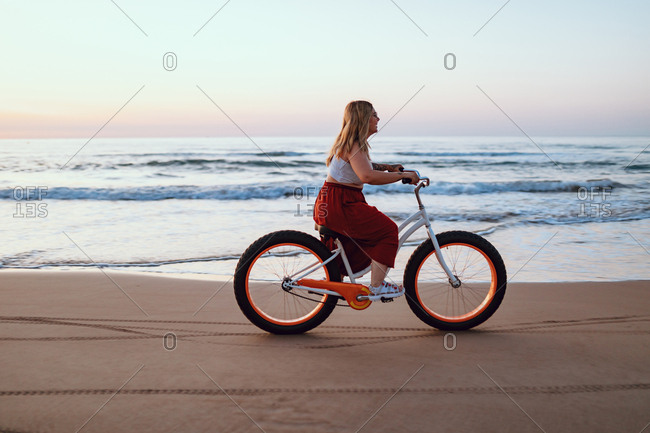 Side view of chubby modern happy woman in bright skirt riding bicycle along scenic ocean shore in twilight