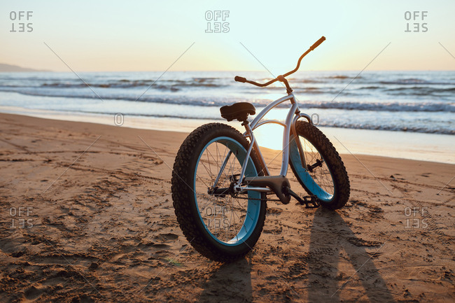 Shiny new fat bike parked at sandy tranquil seaside on summer sunset