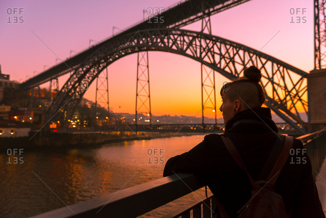 Back view of female tourist standing near city embankment near bridge looking away during sunset in Porto, Portugal