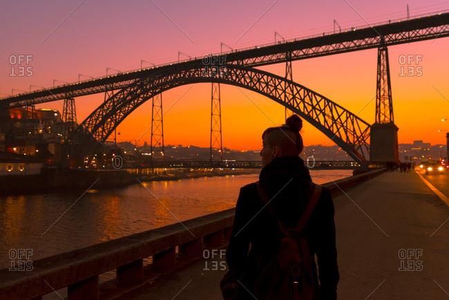 Back view of unrecognizable female tourist walking near city embankment near bridge during sunset in Porto, Portugal