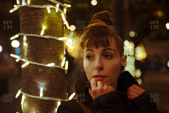 Pretty young female with hair bun and piercing looking away while standing near tree trunk decorated with fairy lights on city street in evening
