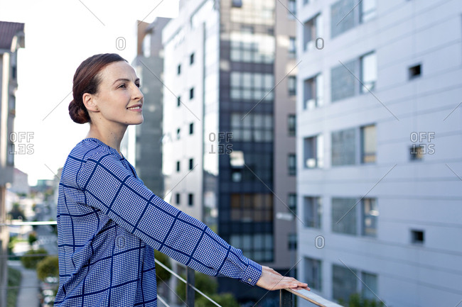 Side view of pretty female manager in checkered shirt smiling and looking away while standing on balcony of office building on sunny day in city