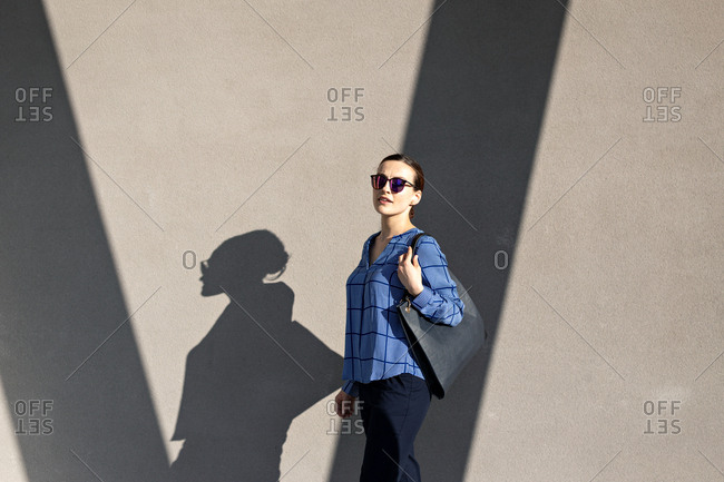 Full body female manager in sunglasses and elegant outfit smiling and looking at camera while standing against gray building wall on city street