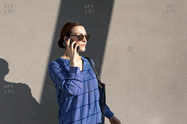 Attractive female manager in blue checkered shirt and sunglasses talking on smartphone and looking away while standing against gray wall on street