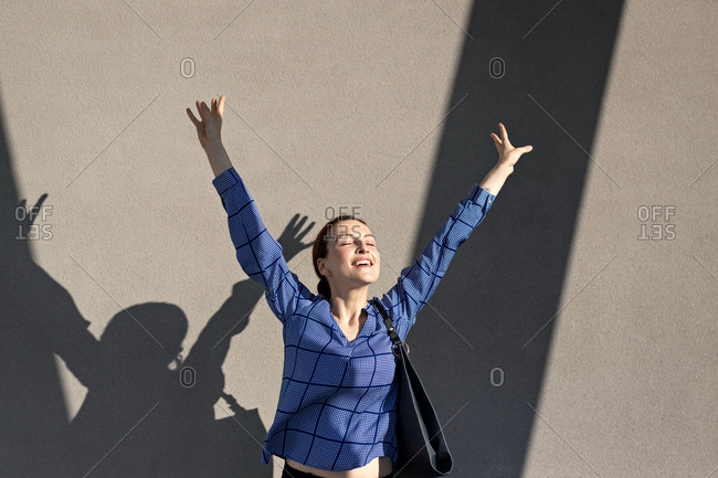 Female manager in elegant outfit raising arms and jumping