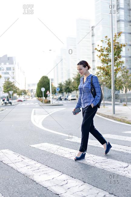 Positive female entrepreneur in elegant outfit holding hand in pocket while walking on crosswalk on street of modern city