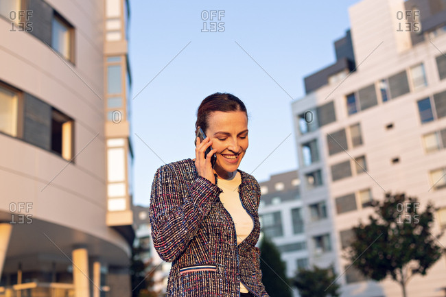 Cheerful female entrepreneur smiling and looking away while talking on smartphone and standing on background of modern buildings and cloudless blue sky