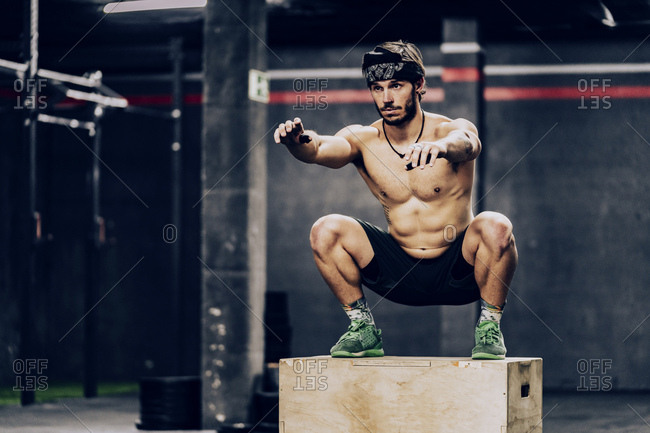 Athletic man jumping on box to improve stamina in gym