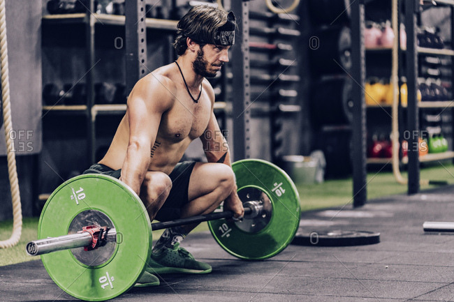 strong and athletic man doing barbell workout in modern gym