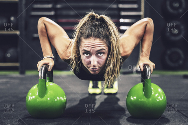 Muscular woman on hands in dumbbells in modern gym on blurred background
