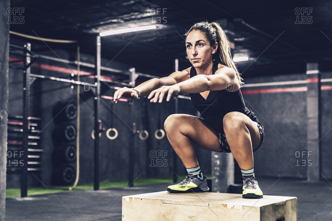 Athletic woman jumping on box to improve stamina in gym