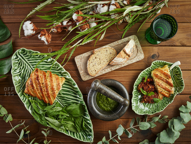 Top view of delicious puff pastry with mozzarella and salmon served on plates near pesto sauce and bread amidst plants twigs on wooden tabletop