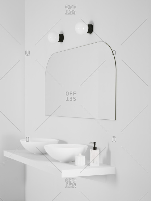 Ceramic bowl placed on simple shelf against white wall in bathroom with mirror