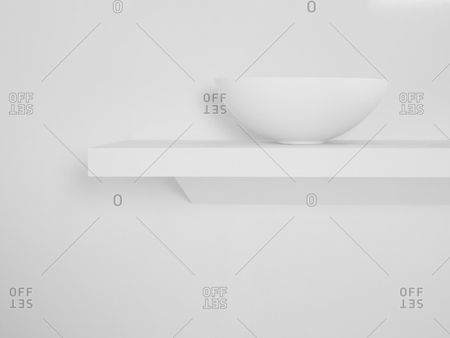 Ceramic bowl placed on simple shelf against white wall in bathroom