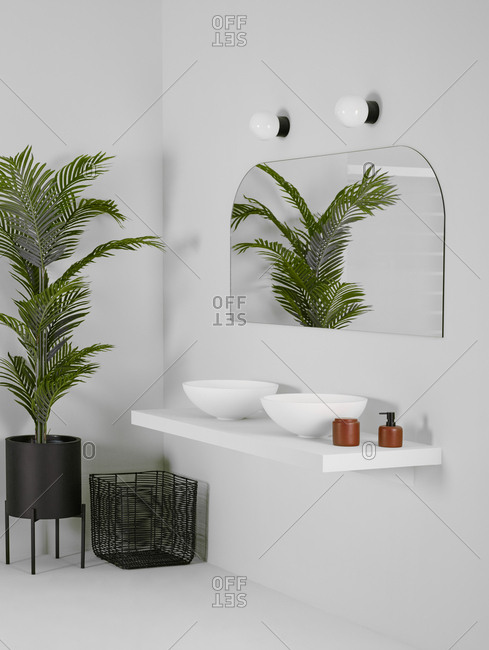 Ceramic bowls placed on simple shelf against white wall in bathroom with mirror and tall plant