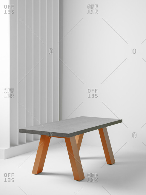 Small trendy table located in middle of modern simple room with white wall and partition