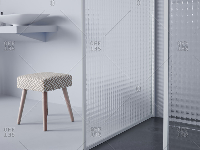 Small trendy stool located in middle of modern simple room with white wall and partition