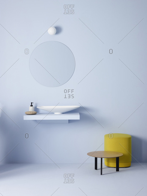 Light bulb and oval mirror hanging on blue wall over sink in minimalist bathroom