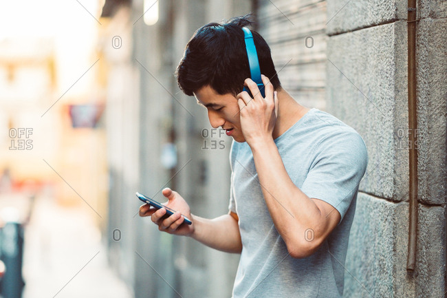 Joyful casual ethnic man in headphones using smartphone while standing on sunny city street