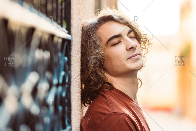 Side view of content relaxed man leaning on wall with closed eyes while standing on sunny street