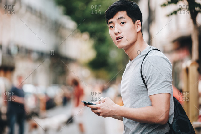 Side view of uncertain ethnic man in t shirt browsing smartphone and looking around while standing on busy street