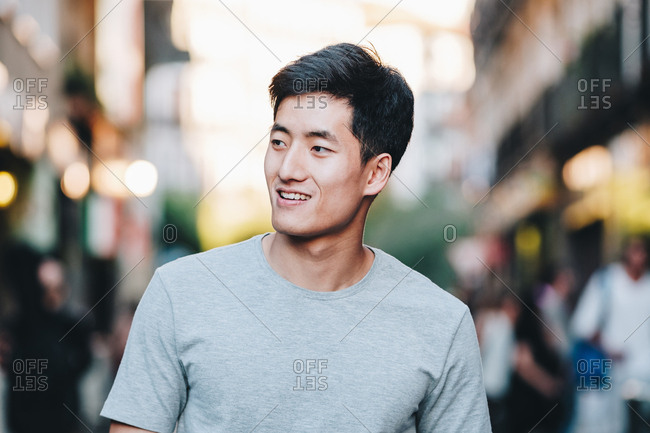 Content modern young ethnic man in t shirt strolling along urban summer street
