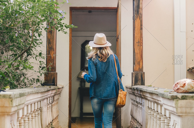 Back view of young woman in denim and hat opening wooden glass door of authentic building