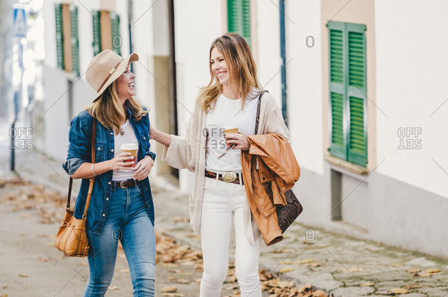 Stylish relaxed woman chatting happily while walking down street having coffee in cups