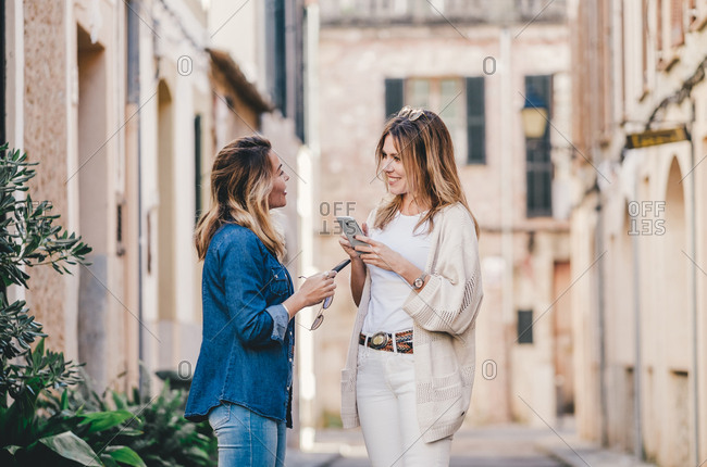 Young attractive smiling women walking and messaging with mobile phones in street