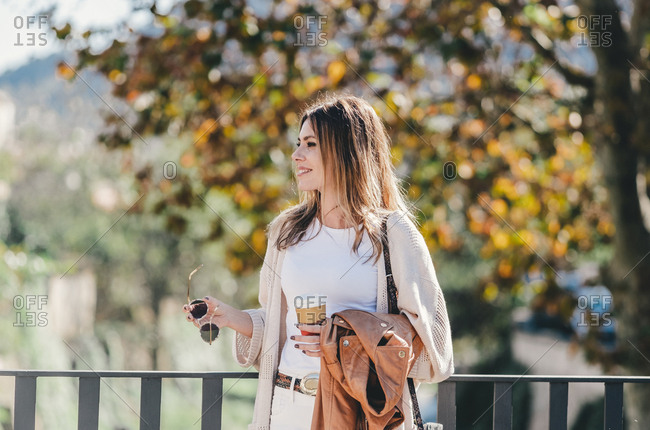 Attractive graceful woman with coffee and jacket in hand looking along leaning on handhold in warm autumn day